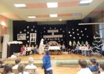 Dzieci z klasy 3e podczas występu. w tle zimowe dekoracje