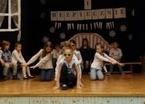 Dziewczynki przykucnięte na scenie rozpoczynają taniec