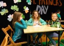 Dzieci ubrane na zielono siedzące przy stoliku