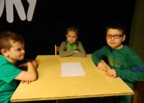 Dzieci ubrane na zielono siedzące przy stolikach