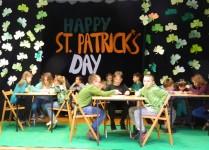 Na scenie przy stolikach siedzą dzieci, w tle zielone koniczynki