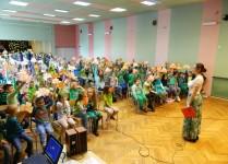 Aula wypełniona dziećmi w zielonych strojach