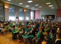 Aula wypełniona dziećmi w zielonych strojach z koniczynkami w rękach