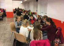 Dzieci przy stolikach czytają książki