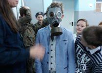 uczeń przymierzający maskę przeciwgazową